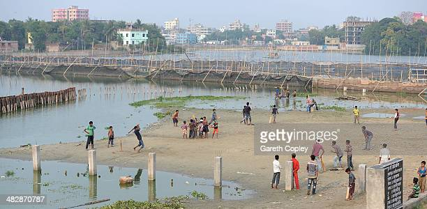 Local children play cricket alongside fishfarms on April 5 2014 in Dhaka Bangladesh