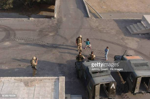 Local children play with British soldiers in the ground of a house belonging to Ali Hassan alMajid the notorious henchman and cousin of Saddam...