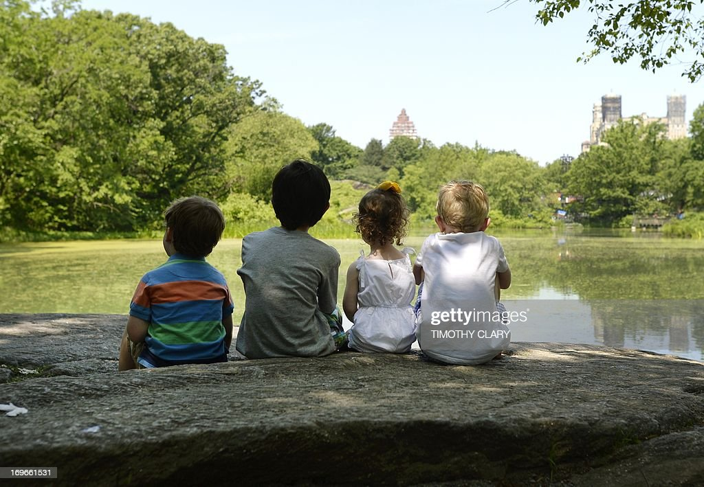 Local children take advantage of the hot weather to sun on a rock at the Lower Reservoir near the Belvedere Castle in Central Park on May 30, 2013 as temperatures were expected to reach in the 90's (30C) in New York City.