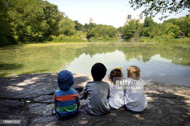 Local children take advantage of the hot weather to sun on a rock at the Lower Reservoir near the Belvedere Castle in Central Park on May 30, 2013 as...