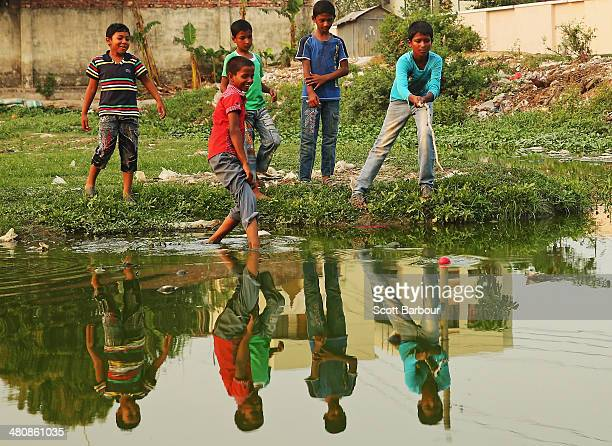 Local children try to retrieve a ball hit into a lake as they play street cricket in the suburbs of Dhaka during the ICC World Twenty20 Bangladesh...