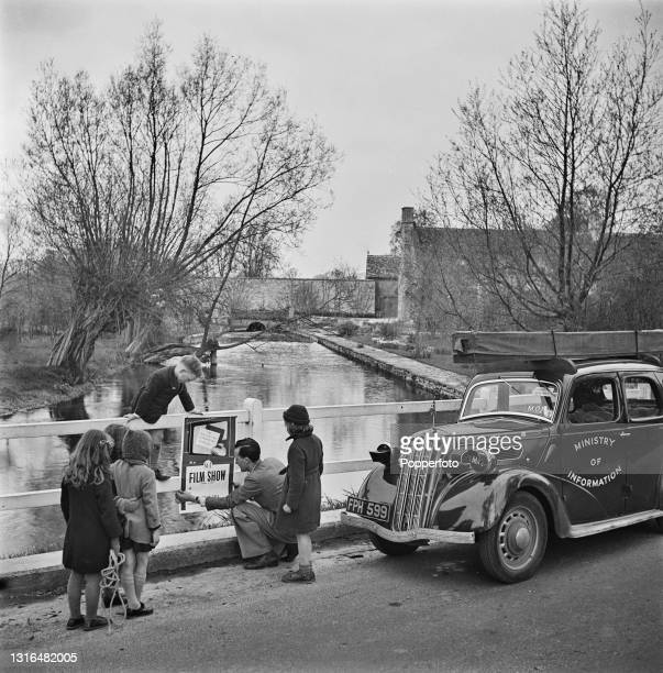 Local children watch as a Mobile Film Unit operator from the Ministry of Information puts up a poster on a bridge in a Cotswolds village during World...