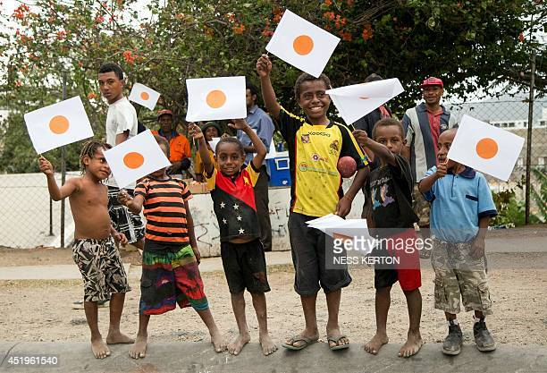 Local children wave Japanese flags as Japan's Prime Minister Shinzo Abe arrives in the Papua New Guinea capital of Port Moresby on July 10 2014 Abe...