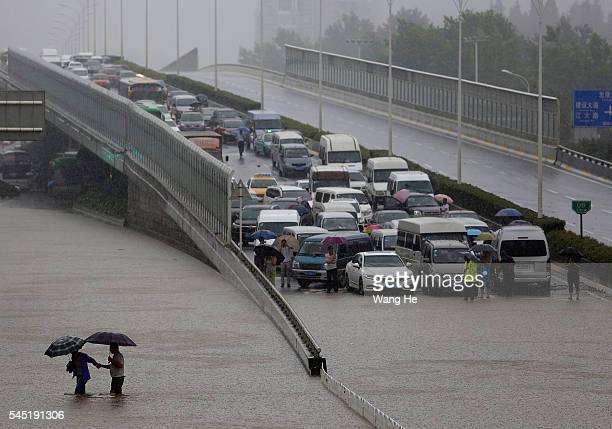Local Chinese residents walk on a flooded street in heavy rain in Wuhan £¬Hubei province China6 July 2016 An overnight storm following days of rain...