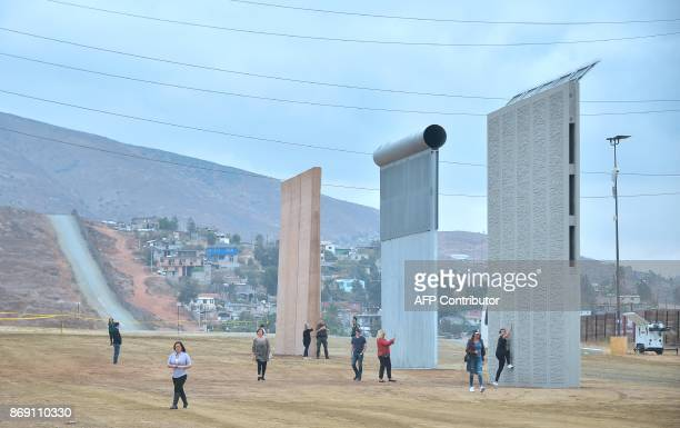 Local city officials visit prototypes of US President Donald Trump's proposed border wall on November 1 2017 in San Diego California The concrete and...