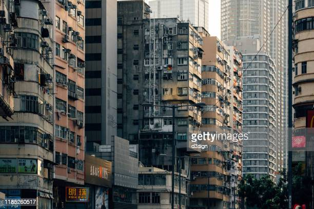 local city street scene with high density traditional residential buildings along with modern architectural buildings in kowloon, hong kong - kowloon fotografías e imágenes de stock