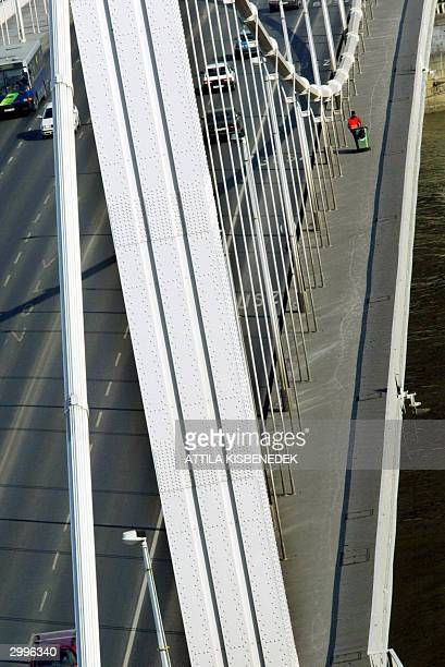 Local clener worker hitches a plastic container on Queen Elisabeth Bridge, a chain suspension bridge, crossing Danube River in Budapest 17 February...