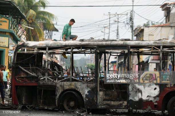 A local climbs onto a bus burnt on the eve during protests after President Nicolas Maduro's government ordered a temporary closedown of the border...
