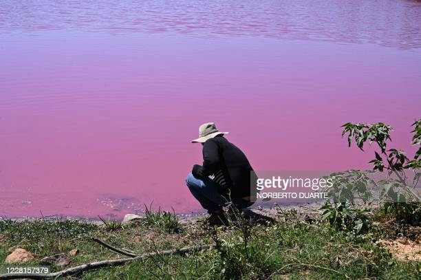 Local collects a sample of water from the Cerro Lake, formed from a meander of the Paraguay River, during a protest against a nearby tannery which...