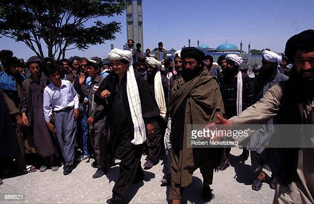 Local commander General Abdul Malik and Taliban leader Abdul Razzaq walk out of the Blue Mosque May 27 1997 in MazariSharif Afghanistan following...