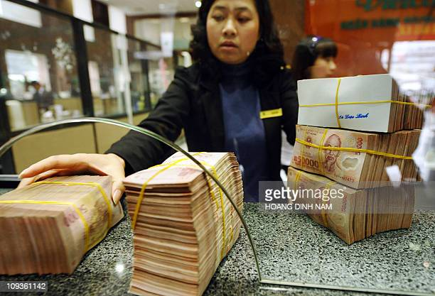 Local commercial bank staff receives bricks of dong bank notes from a customer in Hanoi on February 23, 2011. Vietnam's central bank raised its...