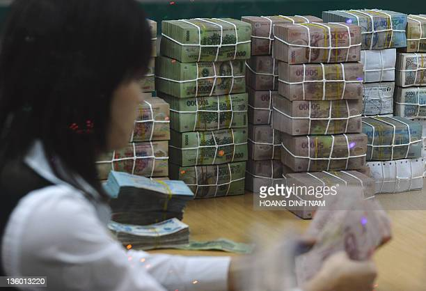 Local commercial bank's employee counts local bank notes, the dong, next to a pile of dong in Hanoi on December 19, 2011. Vietnam's economy is facing...