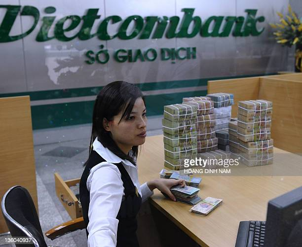 Local commercial bank's employee counts money next to piles of bank notes dong in Hanoi on December 19, 2011. After years of sky-rocketing credit...