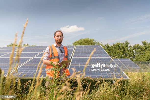 local community member using digital tablet app to look at energy performance of solar farm - environmentalist stock pictures, royalty-free photos & images