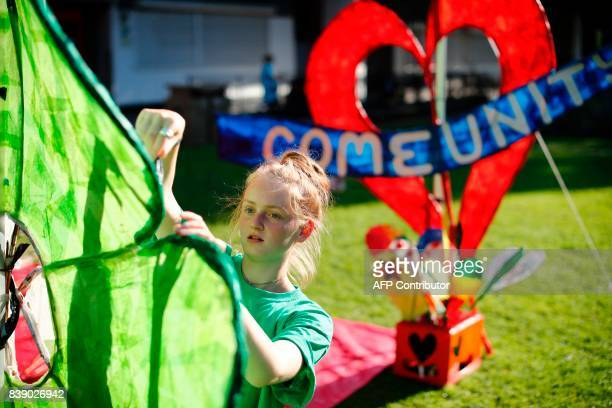 Local community members create posters and banners in Kensington near the burntout remains of Grenfell Tower in London on August 25 2017 ahead of the...