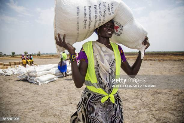 A local community volunteer carries a sack of seeds distributed by the International Committee of the Red Cross in the opposition controlled town of...