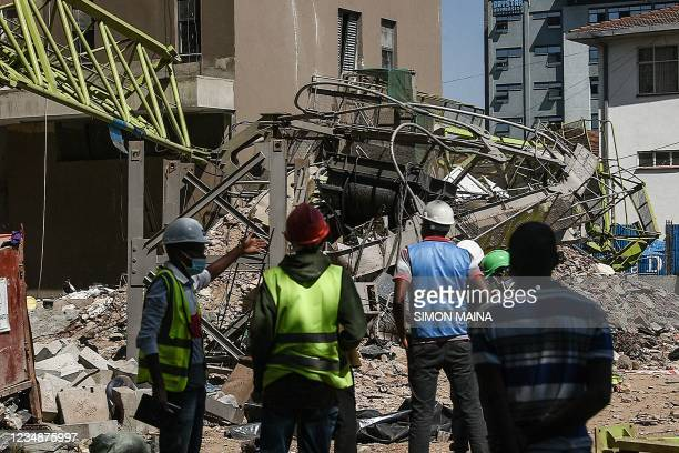 Local contractors standing next to a collapsed crane at a construction site in Kenya's capital Nairobi, on August 26, 2021. - The crane came crashing...