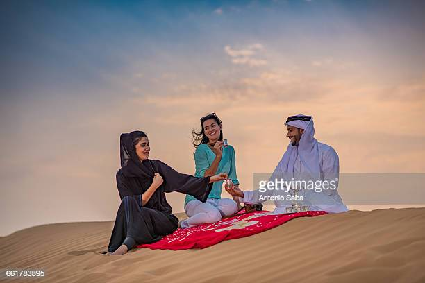 Local couple wearing traditional clothes picnicing on desert dune with female tourist, Dubai, United Arab Emirates