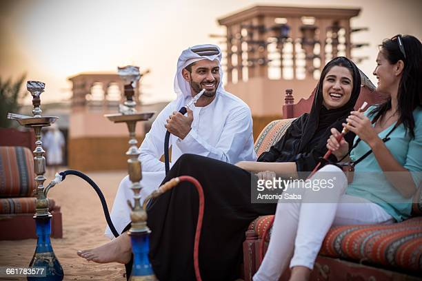 Local couple wearing traditional clothes smoking shisha on sofa with female tourist, Dubai, United Arab Emirates