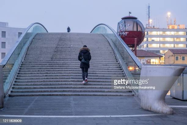 A local crosses the Calatrava Bridge on March 11 2020 A local walks near the Grand Canal with a protective face mask in Venice Italy The Italian...