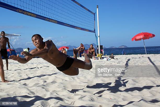 A local dives for the ball while playing foot volley a hybrid game combining beach volley ball and football at Copacabana beach Rio de Janeiro Brazil...