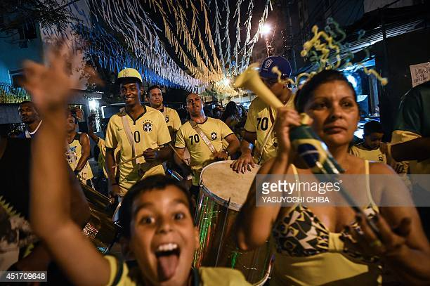 A local drum band marches along the street as children accompany in Jacarezinho shantytown in Rio de Janeiro Brazil celebrating Brazil's 21 victory...