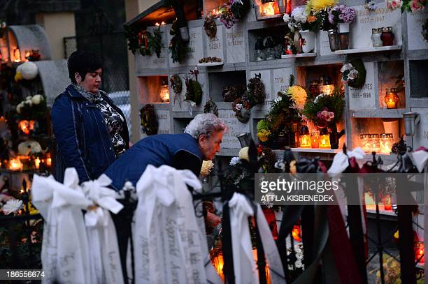A local family lights candles on the occasion of All Saints' Day on the Hatvan street cemetery in Eger Hungary on November 1 2013 In Hungary people...