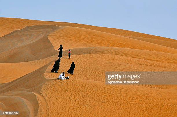 Local family looking for a perfect picnic spot on a desert dune in the United Arab Emirates .