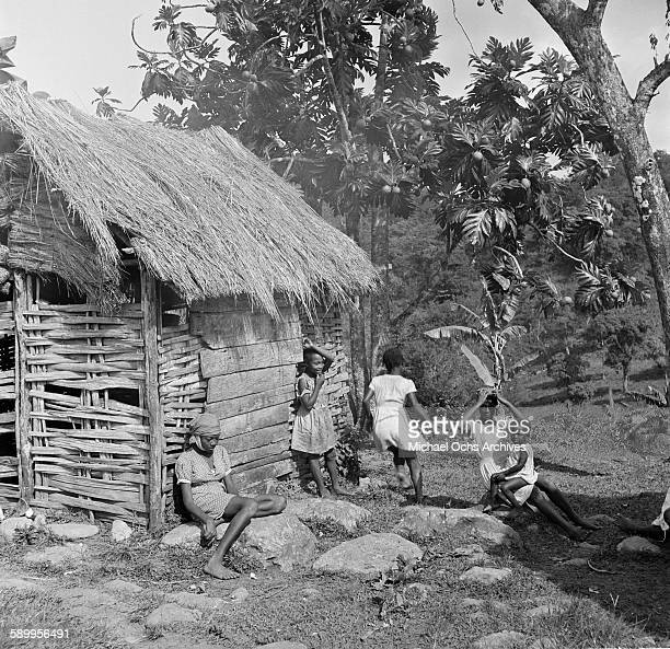 A local family poses outside their home in Jamaica
