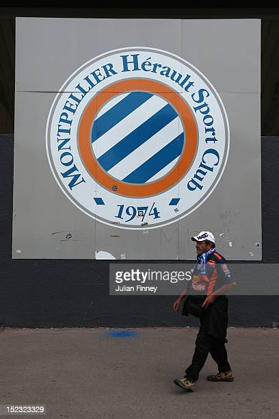 A local fan walks past the stadium logo before the UEFA Champions League match between Montpellier Herault SC and Arsenal at Stade de la Mosson on...