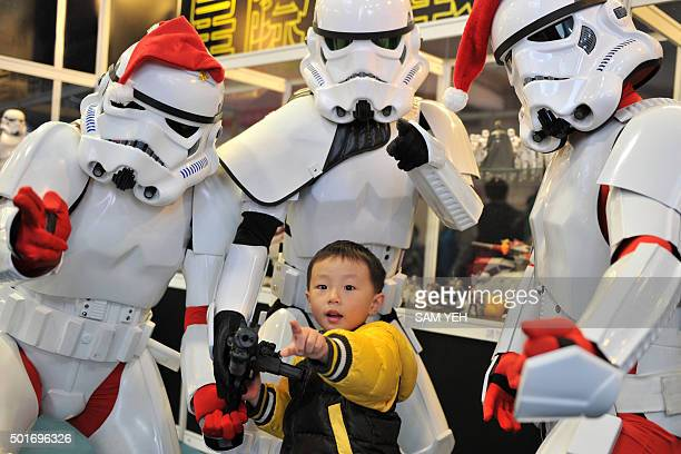 Local fans dressed as Christmasthemed Stormtroopers pose with a child during a toy exhibition in Taipei on December 17 2015 Ever since 1977 when...