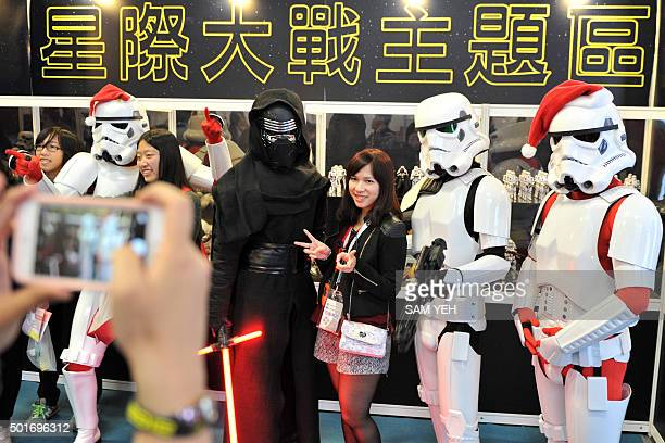 Local fans pose with Star Wars character Kylo Ren and Stormtroopers during a toy exhibition in Taipei on December 17 2015 Ever since 1977 when Star...