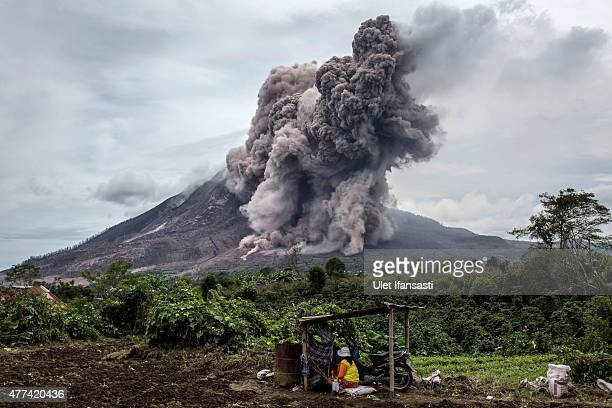 A local farmer sits on her fields as Mount Sinabung spews pyroclastic smoke seen from Tiga Kicat village on June 17 2015 in Sukanalu village North...