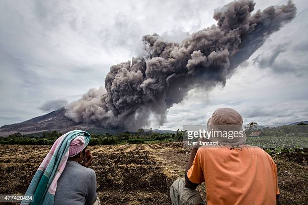 Local farmers pause from their work as Mount Sinabung spews pyroclastic smoke seen from Tiga Kicat village on June 17 2015 in Sukanalu village North...