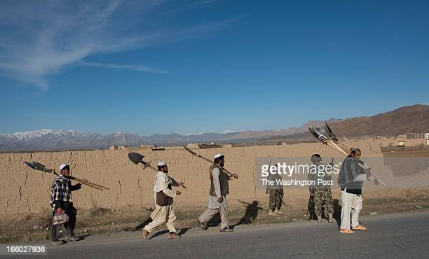 Local farmers walk by Afghan Army soldiers who are checking for IEDs on Saturday March 30 2013 on the Kabul Paktia Hwy in Logar Province Afghanistan...