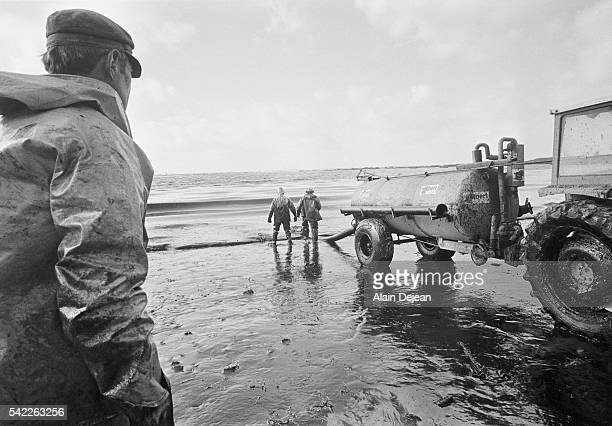 Local firefighters cleaning up oil spread by high winds after the Amoco Cadiz disaster The supertanker Amoco Cadiz ran aground off the coast of...