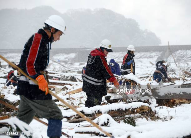 Local firefighters search for people from the March 11 tsunami in a snowcovered field in Miyako in Iwate prefecture on March 16 2011 Japan's Emperor...