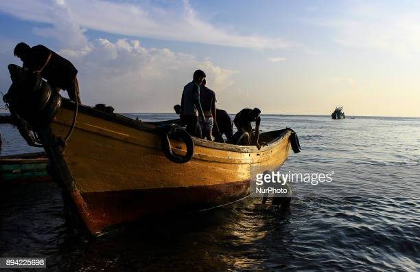 A local fisherman looks to attract fish from the vessel to be marketed in Lhokseumawe traditional market Aceh province Indonesia on December 17 2017...