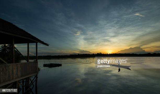 Local fisherman on a lake at sunset in Borneo Kalimantan