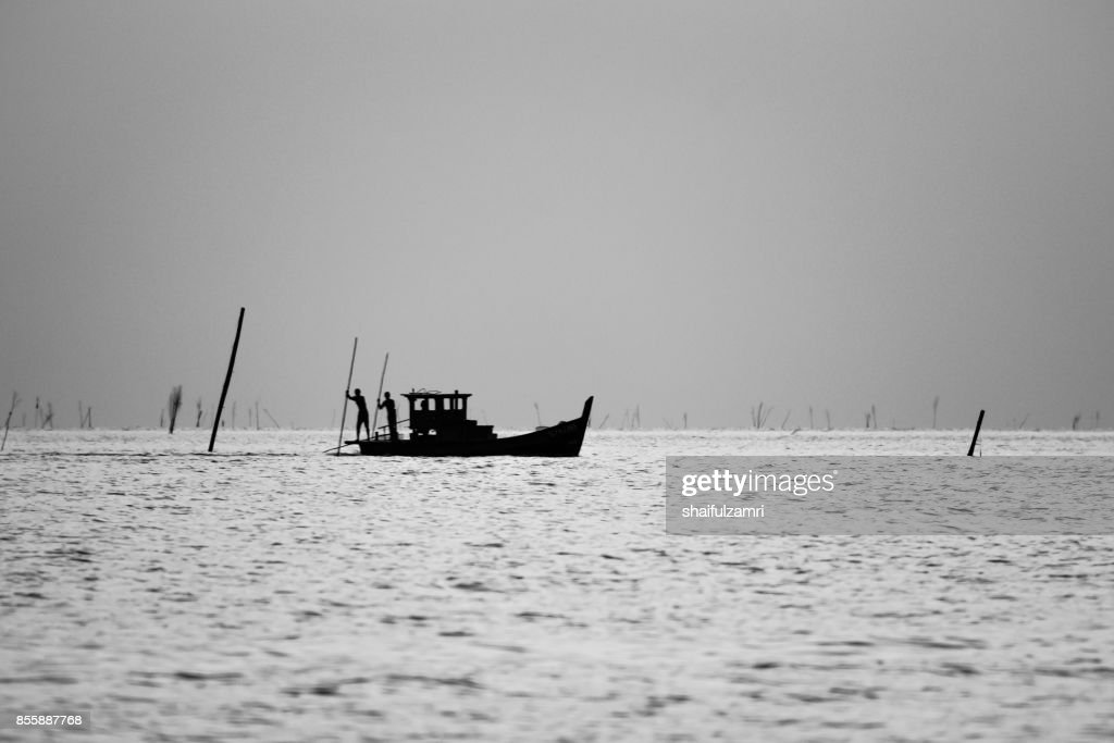 Local fisherman on wooden boat casting a net for fish before sunset : Stock Photo