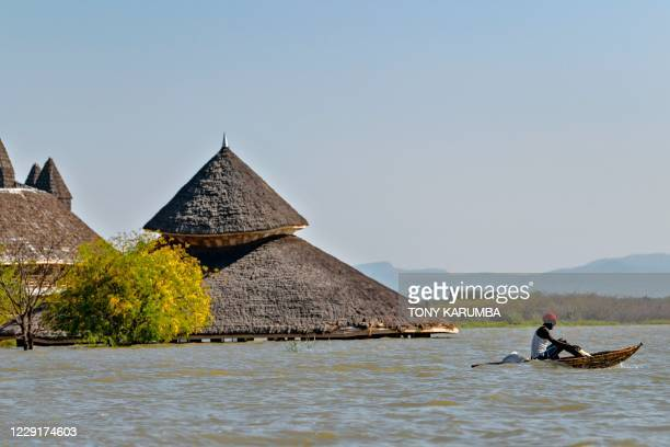 Local fisherman paddles a traditional raft made from reeds past one of the submerged buildings of the Soi Lodge on the shores of Lake Baringo, where...