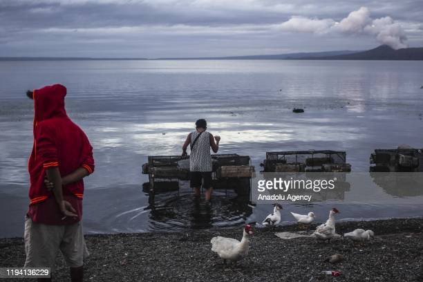 Local fisherman retrieve their livestock fish at Taal lake while the Taal Volcano spews fume on January 17 2020 in Batangas Philippines