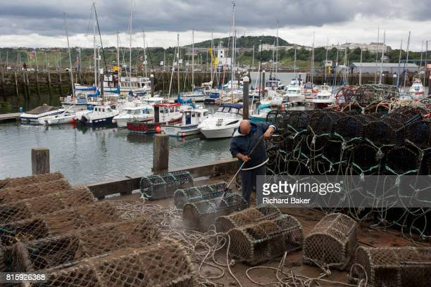 A local fisherman using a jetwash hoses down the seawater off shellfish pots overlooking the harbour on 14th July 2017 at Scarborough North Yorkshire...
