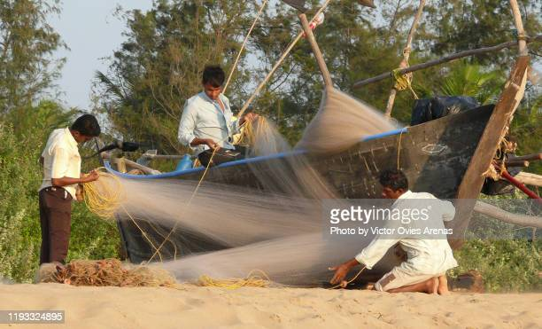 local fishermen preparing their fishing nets at sunset on the beach in gokarna, karnataka, india - victor ovies fotografías e imágenes de stock