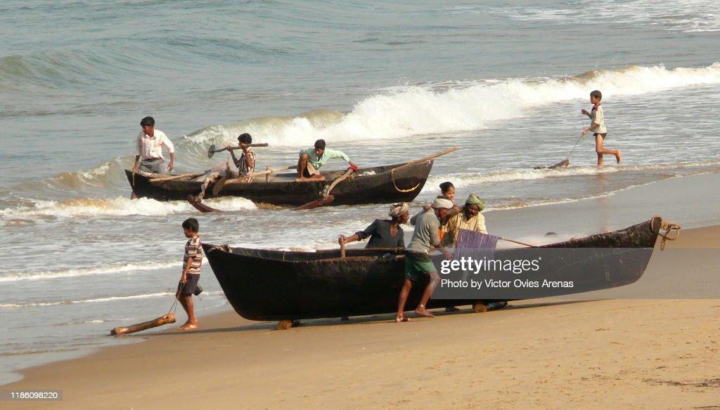 Local fishermen push their fishing boats ashore in Gokarna, Karnataka, India : Foto de stock