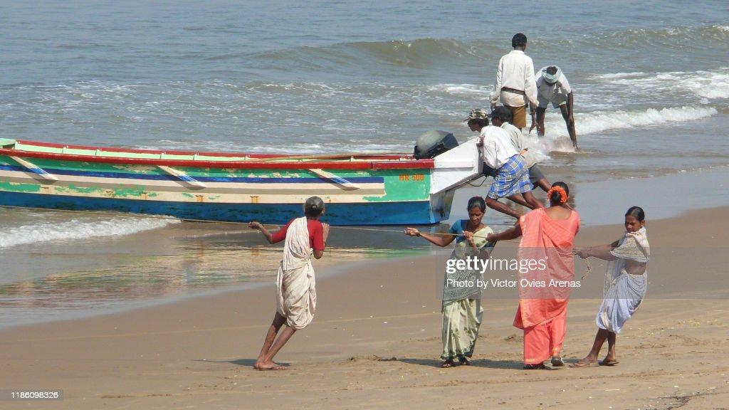 Local fishermen push their fishing boats ashore in Gokarna, Karnataka, India : Stock Photo