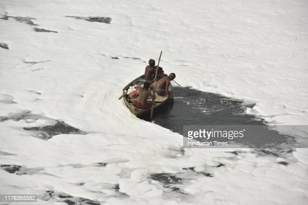 Local fishermen row their boat at the Yamuna River that is covered by froth from discharge of untreated industrial and domestic waste, on October 16,...