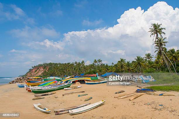 Local fishermen with their boats and tourists spend their holidays at the beach on December 21 2014 in Varkala Kerala India