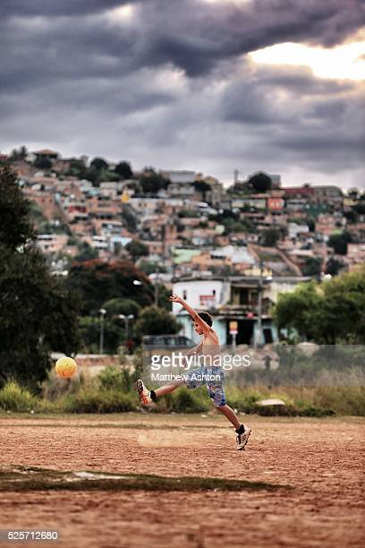 Local footballer kicks a ball on a dust football pitch situated in between Rua Coronel Manuel Assuncao, Belo Horizonte and highway Rodovia Prefeito...