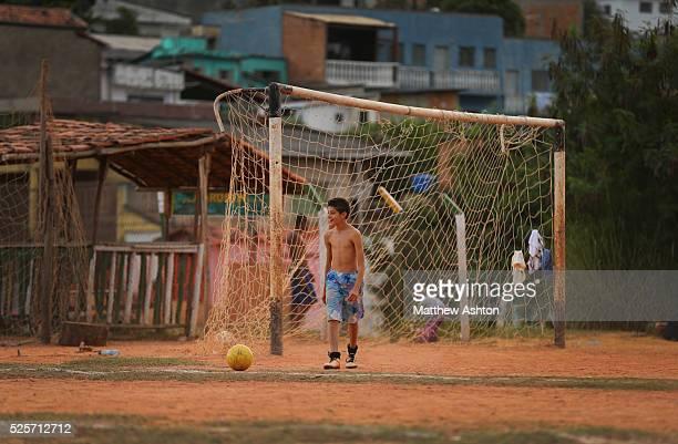 Local footballer kicks a ball on a dust football pitch towards a rusty rustic goal net situated in between Rua Coronel Manuel Assuncao, Belo...